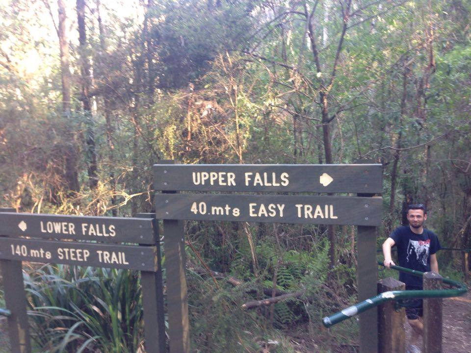 "Signs say ""Lower Falls Steep Trail"" and ""Upper Falls Easy Trail"" with Oli standing by the Easy Trail sign."